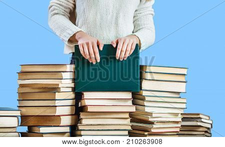 girl hands on the stack of books on blue background