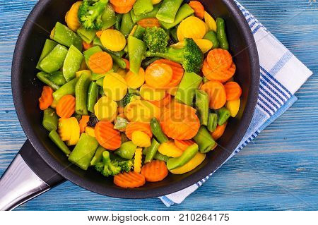 Food for vegetarians. A mix of vegetables on blue background. Studio Photo