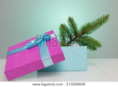 A beautiful gift box in blue, with a purple ribbon and bow. In it lies a branch of a Christmas tree. Beautiful Christmas card on a blue background. An unusual postcard.
