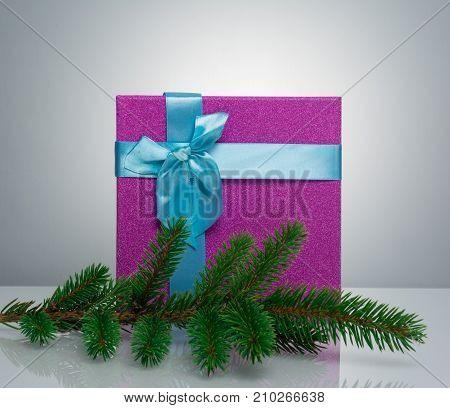 A beautiful gift box in blue, with a purple ribbon and bow. Before her is a branch of a Christmas tree. Beautiful christmas card on white background. An unusual postcard.