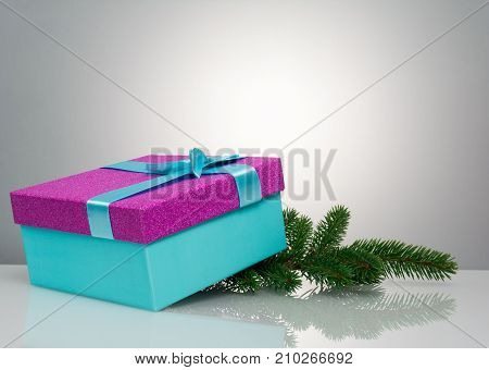A beautiful gift box in blue, with a purple ribbon and bow. Under it lies a branch of a Christmas tree. Beautiful christmas card on white background. An unusual postcard.