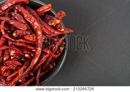 Culinary spice chili pepper on black stone. Studio Photo