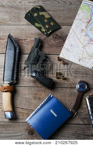 Weapons revolver with bullets and a map on a wooden surface