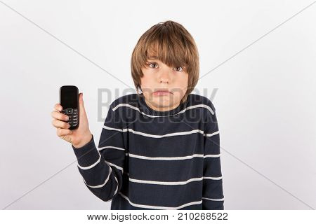 Young boy showing a simple phone is very upset because he would had like a smarthphone rather.