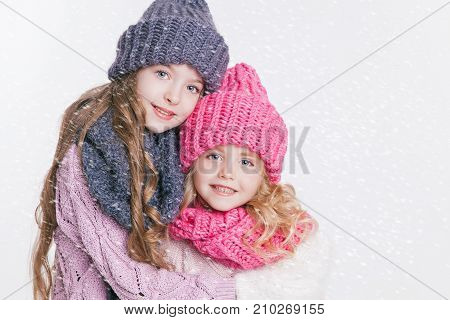 Two little sisters hugging in winter clothes. Hats and scarfs. Pink and grey. Family. Winter. Isolated