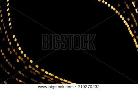 Beautiful Festive Christmas abstract Background with bokeh lights. Holiday greeting card with copy space. Golden light spots on black background defocused. Decorative pattern of the lights