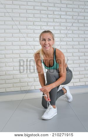 Athletic woman ties up her shoelaces on sneakers at fitness studio