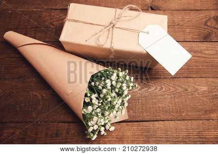 Bouquet of camomile field wrapped in kraft paper on a wooden table