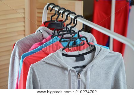 Sport shirts and jackets hanging on clothes rack at a fashion store.