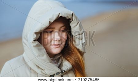 Outdoor portrait of sad young woman girl in hood. Winter time.