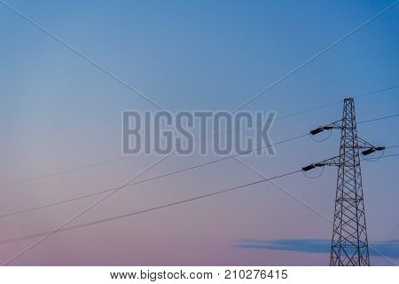 Silhouette of a powerline against clear sky at sunset.