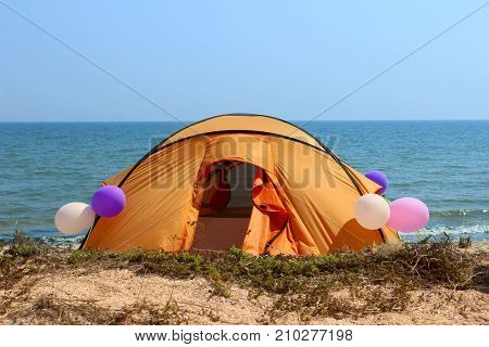 Camping tent in wilderness by the seaside, decorating balloons.