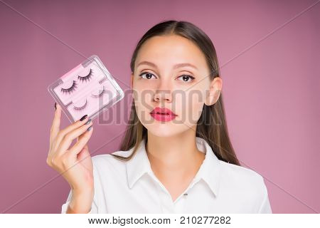 young beautiful girl on a pink background holds in hands a package with black false eyelashes
