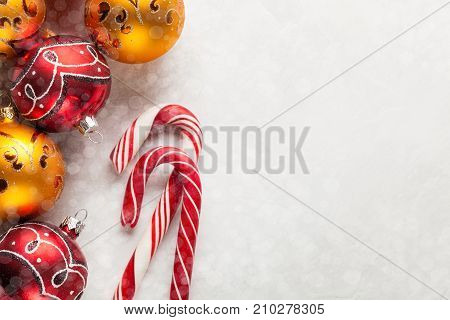 Greeting Card With Christmas Decorations In Red And Gold Balls, Snow And Candy Canes On A White Conc