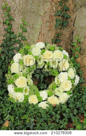 white sympathy wreath or funeral flowers near a tree white roses and mums