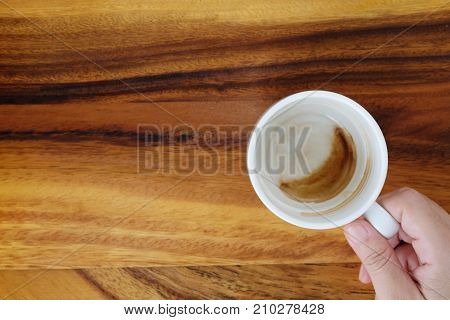 Hand holding a cup with coffee stain cup on wood background with copy space