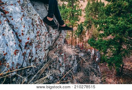 Woman's legs dangling from a rock ledge