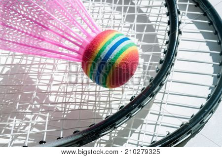 White shuttlecock and badminton rackets lie on a white background.