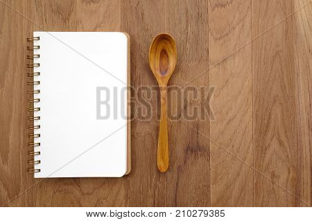 Blank note book and wooden spoon on table cook book background menu food concept flat lay