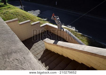 A Young Guy Performs A Jump Through The Space Between The Concrete Parapets. The Athlete Practices P