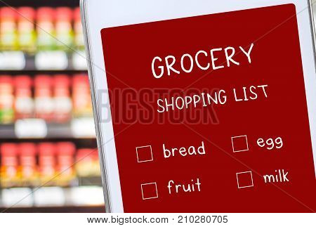 Smart phone with grocery online shopping list on screen over blur product shelves bussiness and technology concept