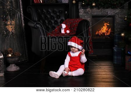 Pretty Little Child In Santa Cap Near Cristmas Tree. The Baby Girl Sits On The Floor Near The Firepl