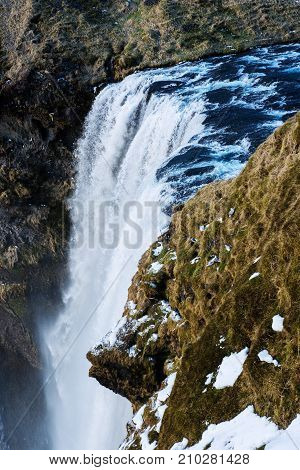 Skogafoss waterfall in Iceland with seagulls on cliff in winter