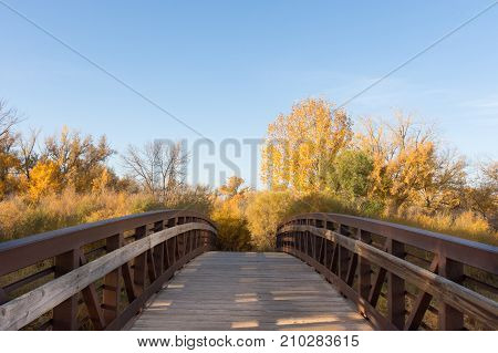 A wooden bridge with shadows across the planks and substantial wood and metal handrails that spans a river surrounding Norm's Island.