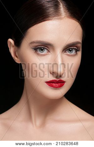 Glamour portrait of beautiful woman model with fresh daily makeup and hairstyle. Fashion shiny highlighter on skin, sexy gloss lips make-up and dark eyebrows. Black background