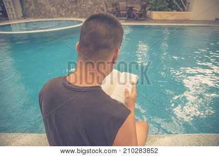 Man enjoy a summer day with favourite book and swimming pool