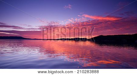 Vivid pink magenta glowing sunrise over water with clear water reflections. Lake Macquarie Australia.