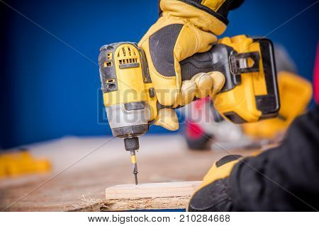 Small Construction Works. Contractor Worker with Cordless Drill Driver Closeup Photo.