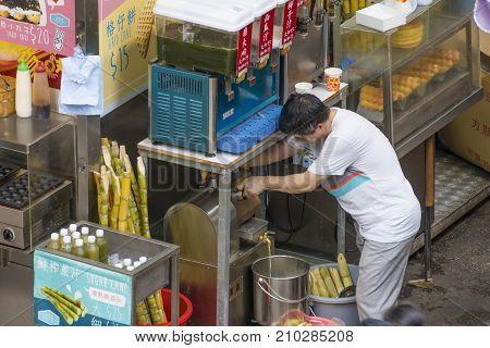 Hong Kong, China - Jun 2, 2017: Man preparing sugarcane juoce at a food stall in Hong Kong selling drinks and street food