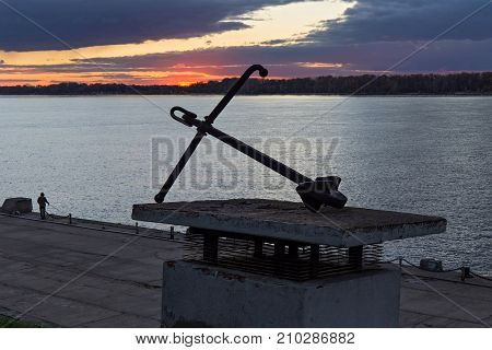 The old iron anchor in the territory of the river station in Samara on the background of a sunset over the Volga River. Russia.