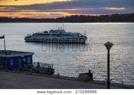 The trip motor ship on the Volga river in autumn evening. Samara city Russia. Near old Volga river station.
