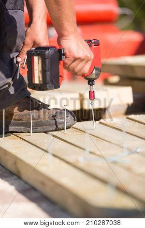Laborer working with cordless battery electric screwdriver on construction site.