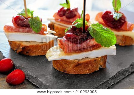 Holiday Crostini Appetizers With Cranberry Sauce, Brie, Salami, And Mint Close Up On A Slate Server