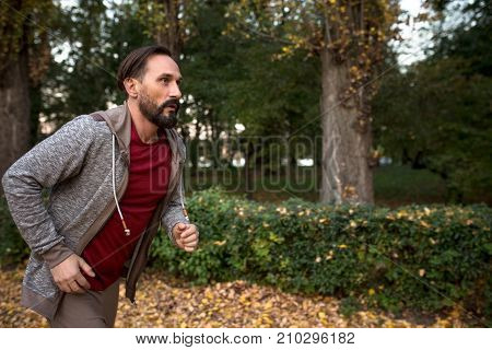 Side view of man running in autumn forest. Healhy male doing cardio workout jogging in city park.
