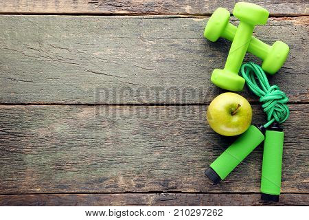 Green Apple, Skipping Rope And Dumbbells On Wooden Table