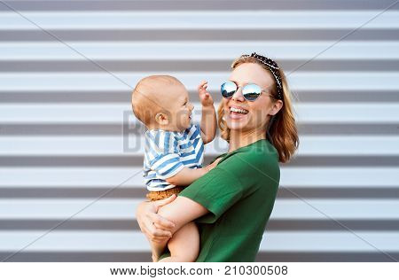 Young woman with a baby boy standing against the wall. Beautiful mother holding her son in arms.