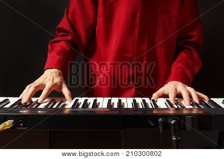 Musician play the keys of the electronic synthesizer on a black background