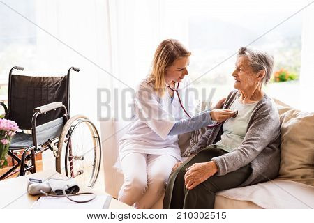 Health visitor and a senior woman during home visit. A nurse or a doctor examining a woman.