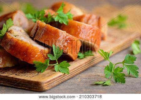 Chicken breast stuffed with stuffing. Sliced chicken rolls, parsley on a wooden board. How to cook stuffed chicken breast. Closeup