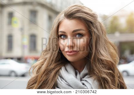 Close up portrait of attractive blue eyed young female with long curly hair and bright make up posing outdoors on street and looking at camera with charming smile. People and urban lifestyle concept