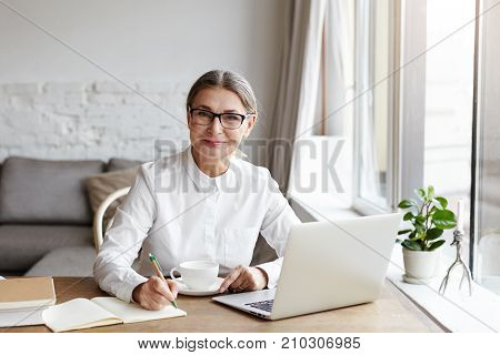 Attractive positive talented mature woman writer sitting in front of laptop and writing her new book about love looking at camera with joyfull smile. Senior female teacher making notes in copybook