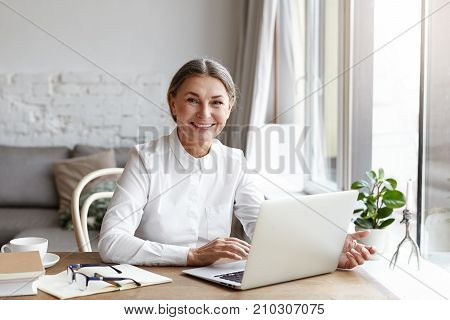 Happy mature woman psychologist or medical expert wearing white shirt working distantly on portable computer consulting her clients online. Senior people modern technologies job and occupation