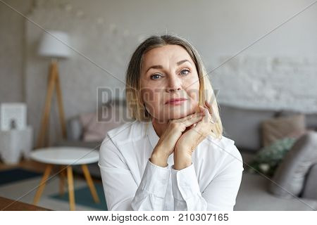 Head and shoulders of beautiful graceful senior woman with healthy wrinkled skin and loose thick hair having rest indoors posing in modern interior looking at camera with thoughtful face expression