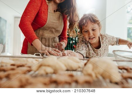 Little Girl Helping Her Mother In Making Cookies For  Christmas.