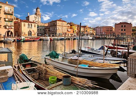 Chioggia, Venice, Italy: landscape of the old town and the canal with fishing boats and ancient buildings