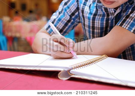 Selective focus on hands of young guest man writing on memory book for blessing word to newlyweds couple in wedding ceremony poster